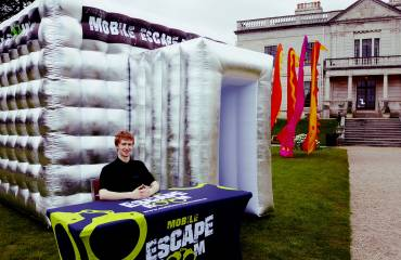 Mobile Escape Rooms inflatable tent with festival flags and staff member